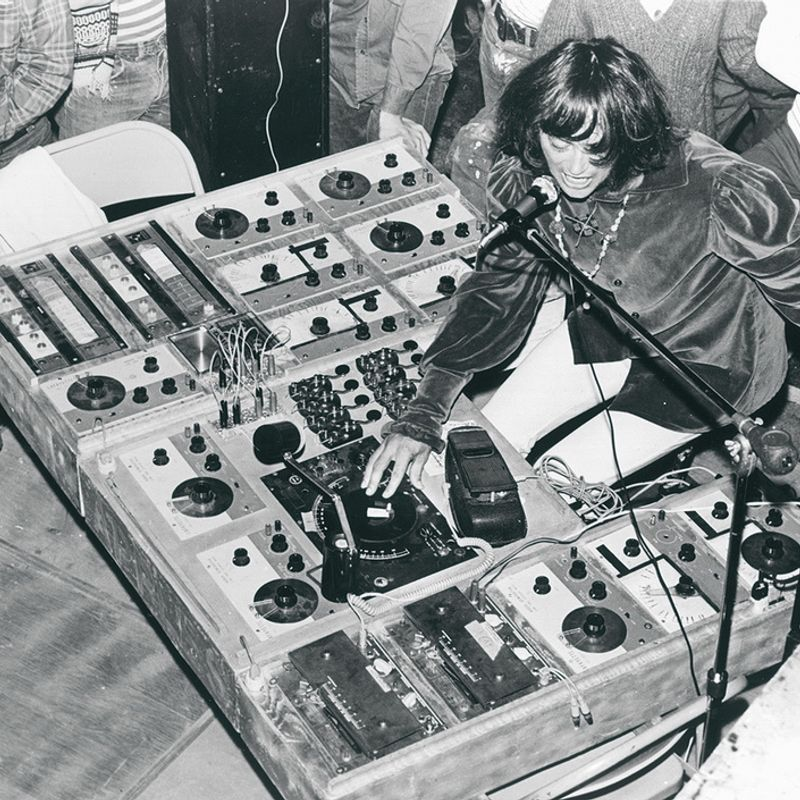 A black and white film photograph of a young Simeon of Silver Apples singing into a microphone and manipulating a complicated looking selection of audio oscillator machines.