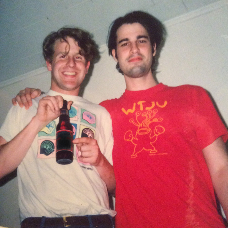 A colour film photograph of a young David Berman with his arm around a young Bob Nastanovich (both of the band Silver Jews). Nastanovich is holding and pointing to a beer bottle. Berman is wearing a red WTJU tee shirt with art that looks like it's one of Daniel Johnston's frog like creatures but with many eyes on stalks.